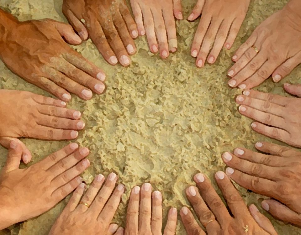 Photo of a circle of hands in the sand