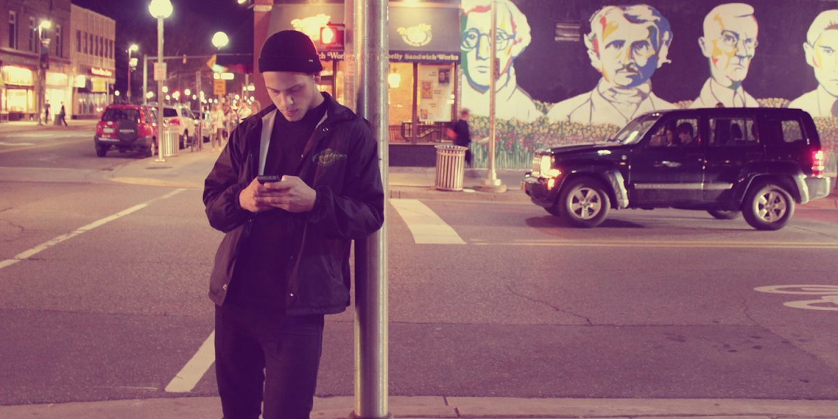 Young guy texting on the street